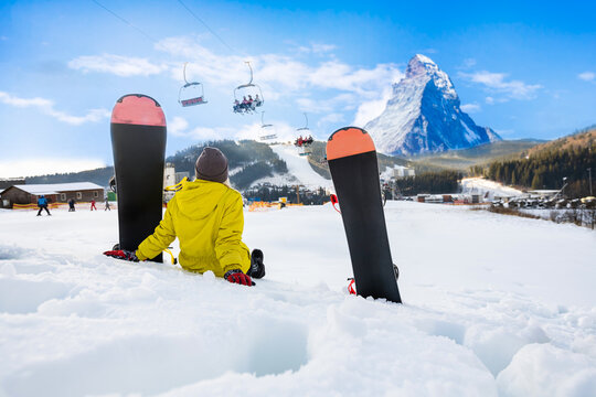 Young woman with snowboard on the slope of hill at winter resort