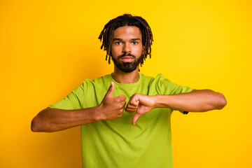 Photo of serious dark skin guy show thumb up thumb down symbol isolated over vivid yellow color background