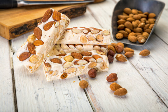 Turron blocks with almonds and hazelnuts on rustic table