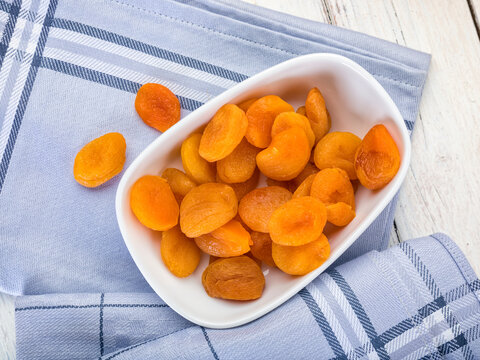 Dried apricots in bowl on table, high angle view