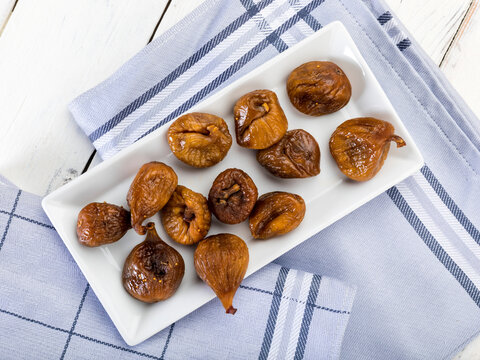 Dried figs in bowl on table, high angle view