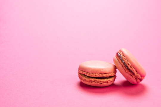 Raspberry flavor macaron cookies on pastel pink colored background