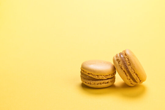 Lemon flavor macaron cookies on pastel yellow colored background