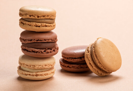 Variety of french macarons pastry on light brown background