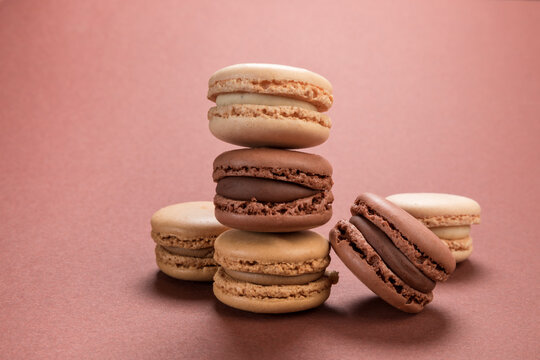 French macarons pastry with vanilla, coffee and chocolate flavours on brown background