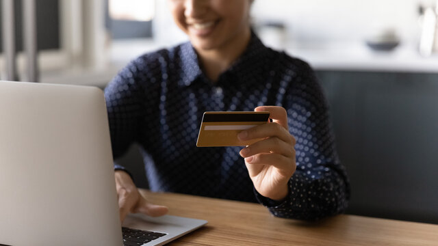 Close up view of happy woman sit at desk shopping online on computer with credit card. Smiling young female buyer pay on internet on laptop use secure banking service system app on gadget.