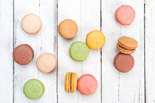 Colorful French macarons pastry on rustic table flat lay top view