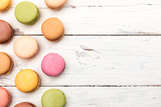 Rustic wooden background with colorful macarons pastry and copy space