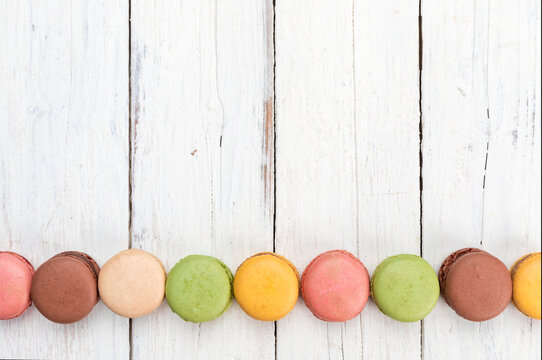Colorful row of French macarons pastry on rustic table flat lay top view