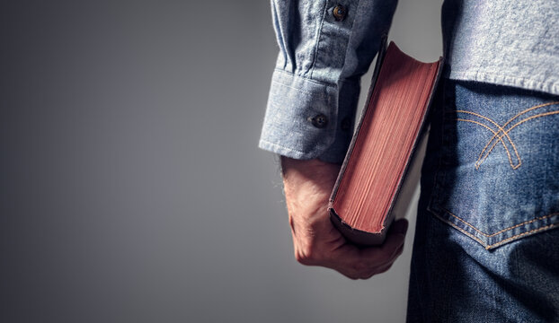 Man holding holy bible with gray background for text