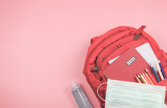 Top view of red 2021 diary in backpack with school supplies , surgical mask and alcohol sanitizer gel on pink background with copy space.COVID-19 prevention, back  to school in 2021  and new normal.