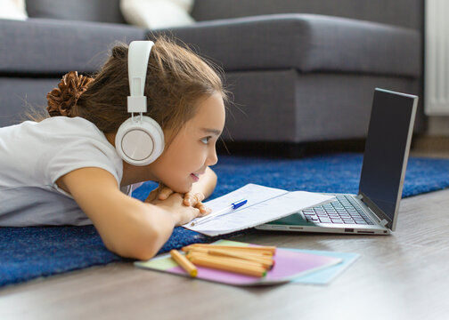 A teenage girl lying on the floor listening to the school program at home online in front of a laptop monitor.