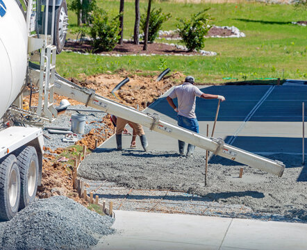 Unidentifiable hispanic men working on a new concrete driveway at a residential home, focus on concrete chute