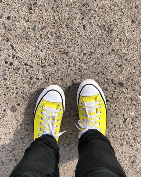 Low Section Of Person Wearing Yellow Shoes On Footpath