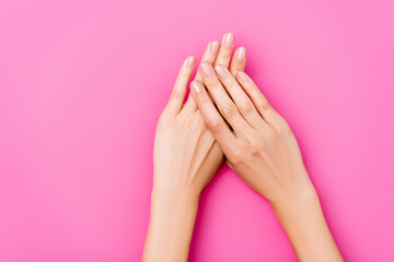 top view of groomed female hands with glossy fingernails on pink background