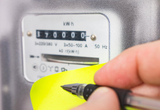 Hand with ballpoint pen writes the readings of the electricity meter. Electricity cost, utility bills concept image