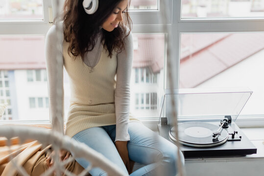 young african american woman in wireless headphones sitting near record player on windowsill, blurred foreground