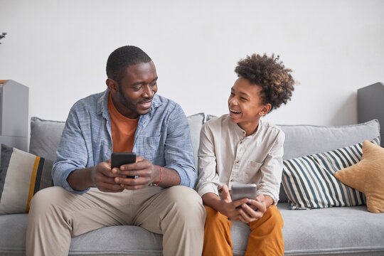 Joyful teenager having fun with his father playing video game on smartphones together while staying at home, medium long shot