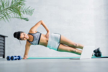happy african american sportswoman exercising in side plank pose on fitness mat near laptop and dumbbells