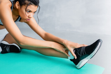 young african american sportswoman doing stretching exercise on fitness mat at home