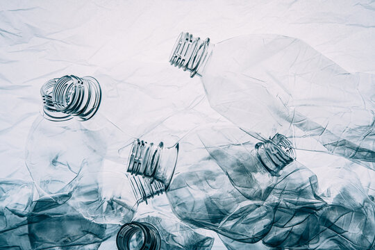 Plastic pollution. Waste management. Ocean conservation. Garbage pile of used empty bottles floating underwater on wrinkled polyethylene texture background with negative effect.