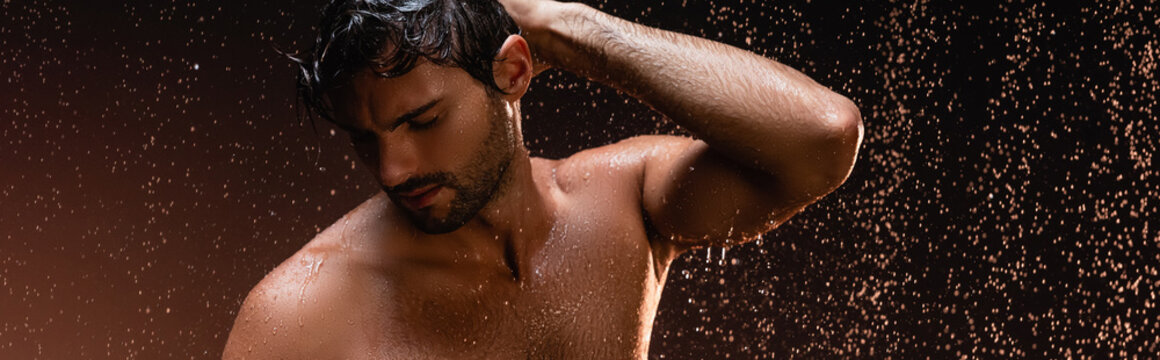 sexy shirtless man posing with closed eyes under rain on dark background, banner