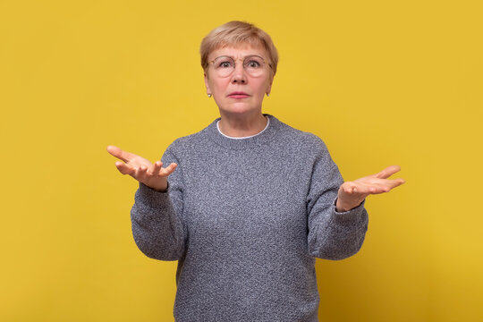 Senior mother shrugging raising palms aside questioned arguing.
