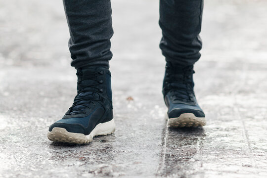 People slides on path. Icing on sidewalk, slippery ice-crusted ground.