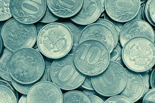 Surface of many Russian coins of 10 ten rubles. Yellow green tinted background or wallpaper. Money backdrop on an economic, financial or banking theme in Russia. View from above. Macro