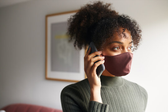 Woman wearing face mask making call on mobile phone before leaving home during health pandemic