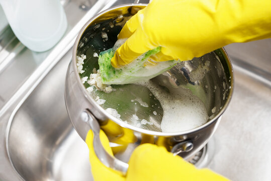 Hands in yellow gloves washing the pan