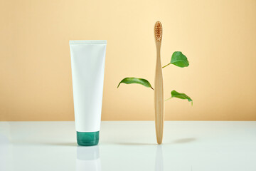 Wooden bamboo toothbrush with leaves on pastel background. Natural organic bathroom toothpaste. Zero waste, Eco-friendly concept.