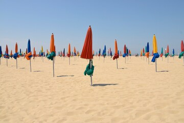 Obraz Folded Beach Umbrellas Against Clear Sky - fototapety do salonu