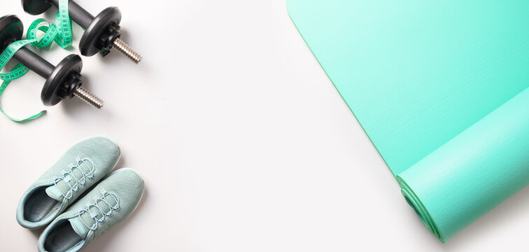 Banner of fitness equipment, dumbbells, yoga mat, shoes on grey. View from above, space for text.