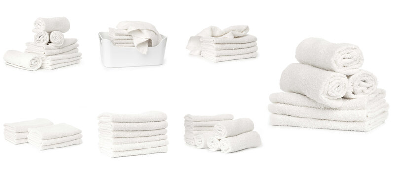 set of white spa towels stacked and in basket isolated on white background
