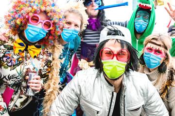 Karneval Party. Gruppe freuliche junger Leute feiern Fasching mit Atemschutz-masken. Corona Konzept.