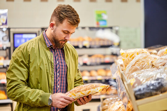 man chooses a fresh bread loaf in the supermarket, in grocery store. man choose food at produce department of shop