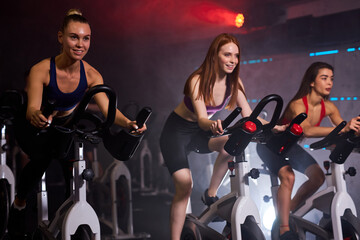 group of sporty people in gym, perfect shaped muscular people training on bicycle, cardio workout at fitness gym, taking weight loss with machine