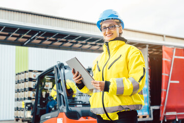 Supervisor checking contents of shipment to be sent by truck