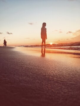 Girl Standing At Beach Against Sky During Sunset