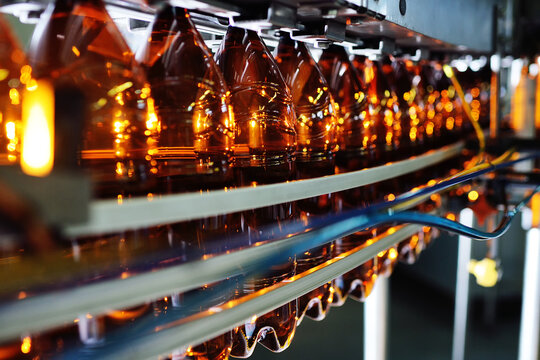 Industrial production of plastic bottles for low-alcohol beverages, soda and sunflower oil. Empty PET bottles of brown color on the background of modern equipment.
