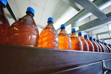 The production of beer. Large brown plastic bottles with blue lids with beer move along the conveyor belt against the background of the brewery. Fotobehang