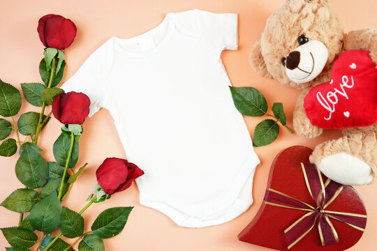 Happy Valentine's Day baby apparel flatlay owith teddy bear, red roses and heart shaped gift on modern coral background. Mock up with negative copy space for your text or design here.