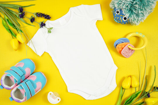 Springtime baby apparel flatlay on bright yellow table with colorful accessories. Mock up with negative copy space for your text or design here.