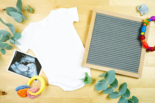 Light natural theme baby apparel top view flat lay with white bodysuit, bib, letter board notice board, for clothing mockups and pregnancy and birth announcements. Mock up