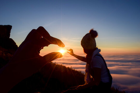 Close-up Of Person Gesturing While Woman Looking At Sun Against Sky During Sunset