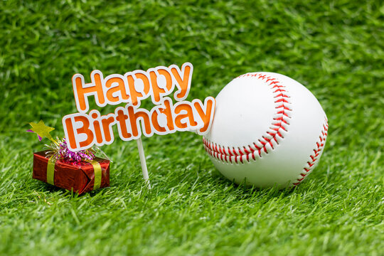 Baseball birthday with sign and baseball gifts on green grass background