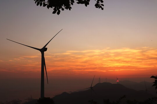 Silhouette Wind Turbines On Mountains Against Romantic Sky At Sunset