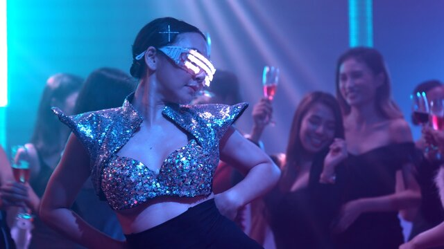 Group of people dance in disco night club to the beat of music from DJ on stage . New year night party and nightlife concept .