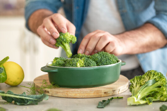 Male hands preparing diet healthy food of baked broccoli at home kitche
